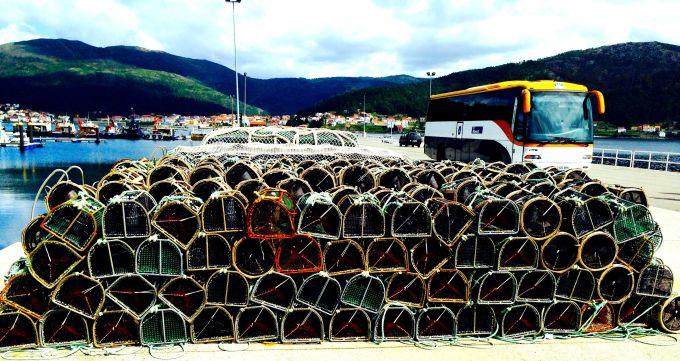 Traps, fishing boats, and a tour bus in the seaside town of Muros.