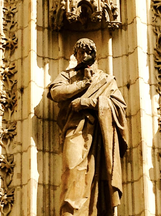 A bird roosting on a statue on the exterior of the Seville Cathedral.