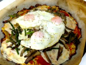 Cauliflower crust pizza with tomato sauce, asparagus and fried eggs